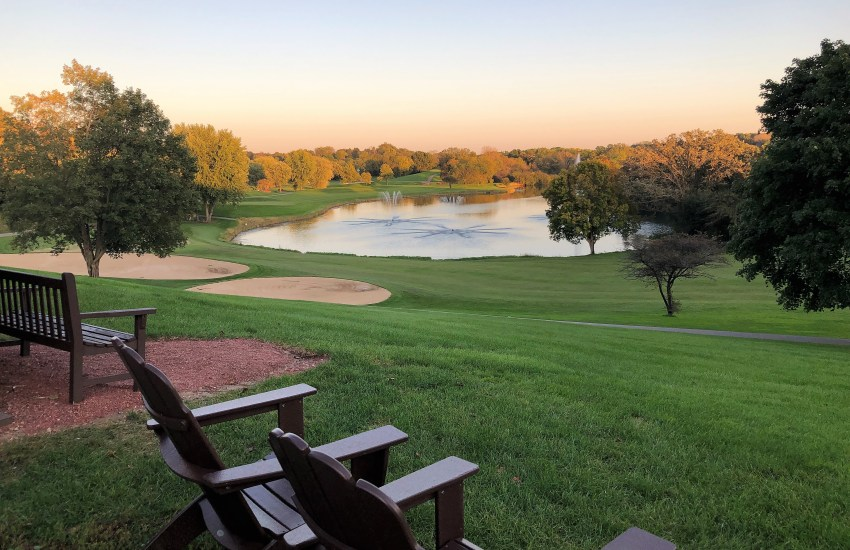 Two wood chairs and a bench overlooking grass, golf course, lake and trees