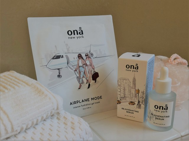 An arrangement of folded towels, Ona Airplane Mode mask packet, box of Ona Rejuvenating serum and the unboxed serum.