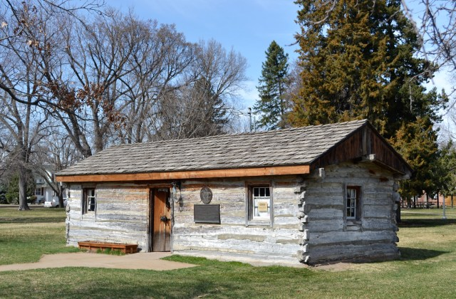An old small log cabin in a park setting.