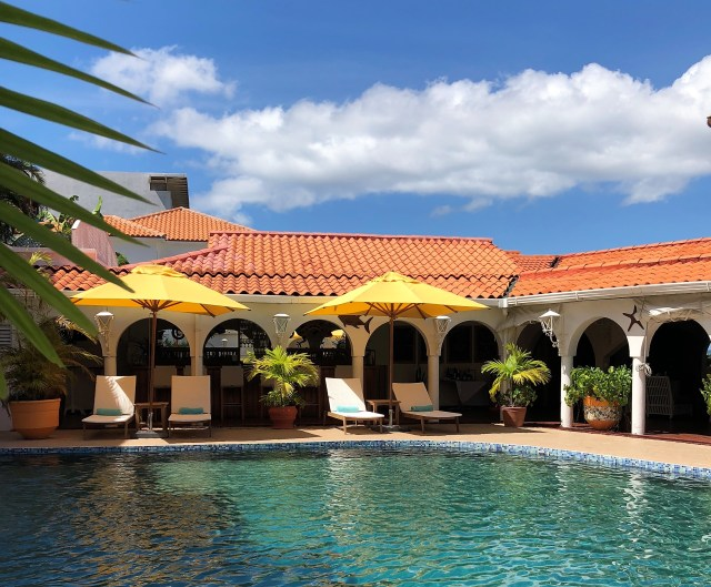 A swimming pool surrounded by two yellow umbrellas, beach chairs and brick-tiled building.