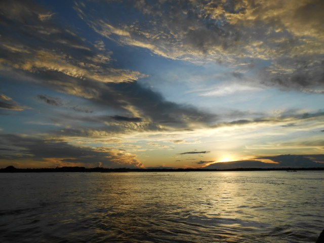 Expansive gray waterway with cloud-filled sky and sun peeking out at horizon, sunset
