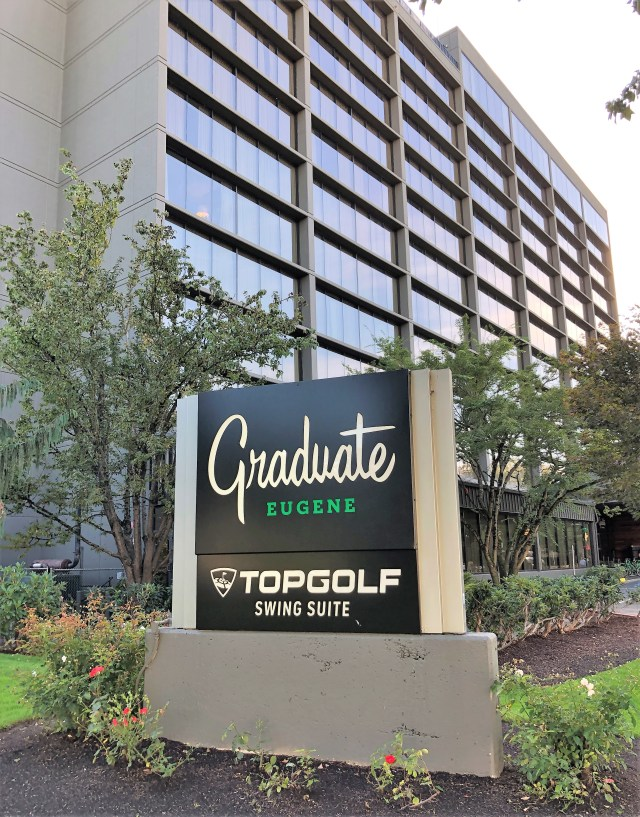 "A sign reads, ""Graduate Eugene, Topgolf Swing Suite,"" in front of a concrete and glass building."