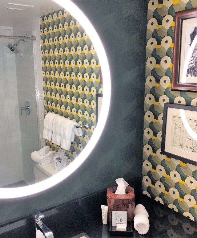 Corner view of a bathroom vanity with one wall reflected in the mirror on the other. The wallpaper is an optical illusion--one view a design of circles and lines, the other view rows of ducks