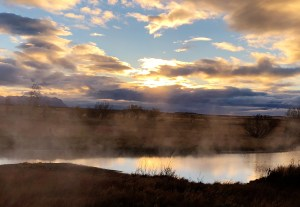 Sun sets behind fluffy clouds, while steam emanates from a river