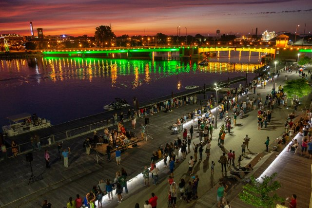 Downtown city scene at night, a yellow and green lighted bridge in the background, throngs of people are gathering along the paved shoreline