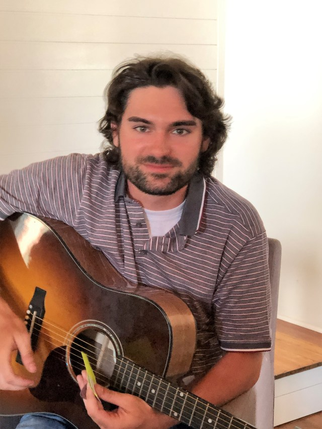 Andrew Groom, a young man with dark curly hair wearing a striped shirt holding a guitar and smiling at the camera