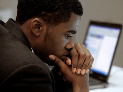 Terrell Collins, of Detroit, pauses while checking employment on a laptop comuter while attending a job fair in Livonia, Mich., Wednesday, Nov. 4, 2009.   (AP Photo/Paul Sancya)