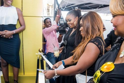 Funke Babs Kufeji cutting the rope flankedby the designer