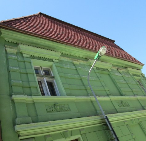 A green street light in front of a green house, Brasov, Romania. Image by @PatFurstenberg