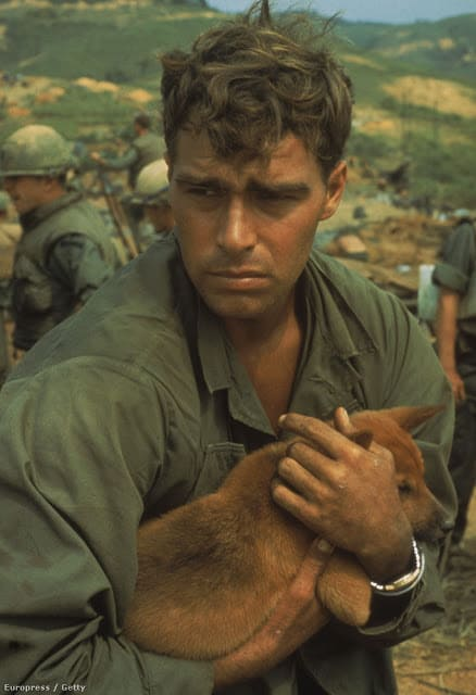 A solder looking distraught though while holding his puppy dearly. Source: history collection