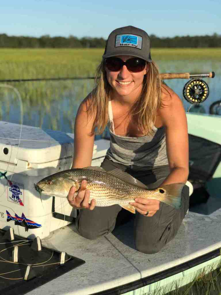 Female holding redfish on a boat that was caught with the Lamson Liquid fly reel.