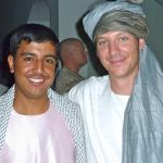 Alastair, wearing a traditional Pashtun outfit, bonds with a local government official in Helmand Province, Afghanistan.