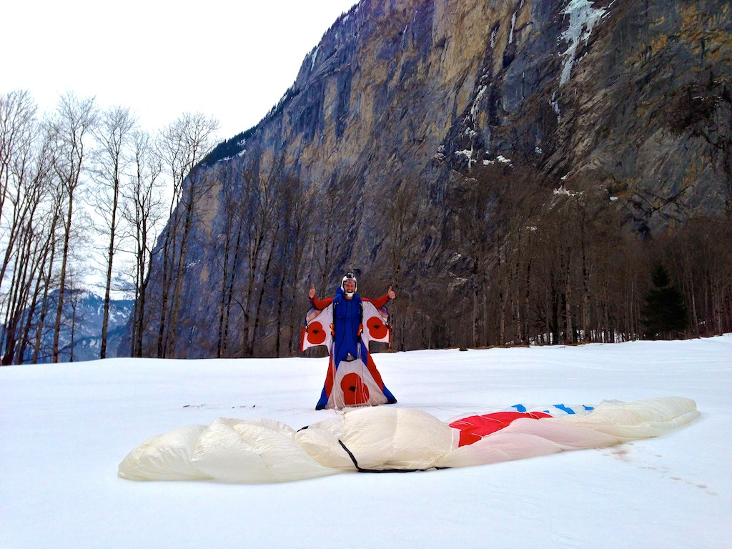 Alastair Macartney poses for a photo in the landing area just having landed from a wingsuit BASE jump.