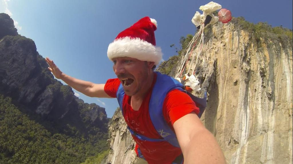 Alastair Macartney BASE Jumps in a Santa Hat from Tonsai Wall, near Krabi, Thailand to raise awareness for those that can't be with their families at Christmas.