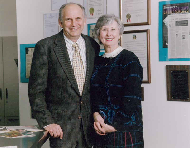 Sam & Mary Gromowsky posed in front of awards.
