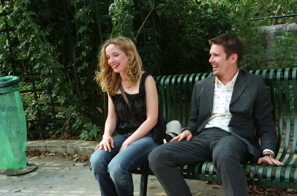Before Sunset (2004) film still of Celine and Jesse sat on a green beach on Promenade Plantee in Paris