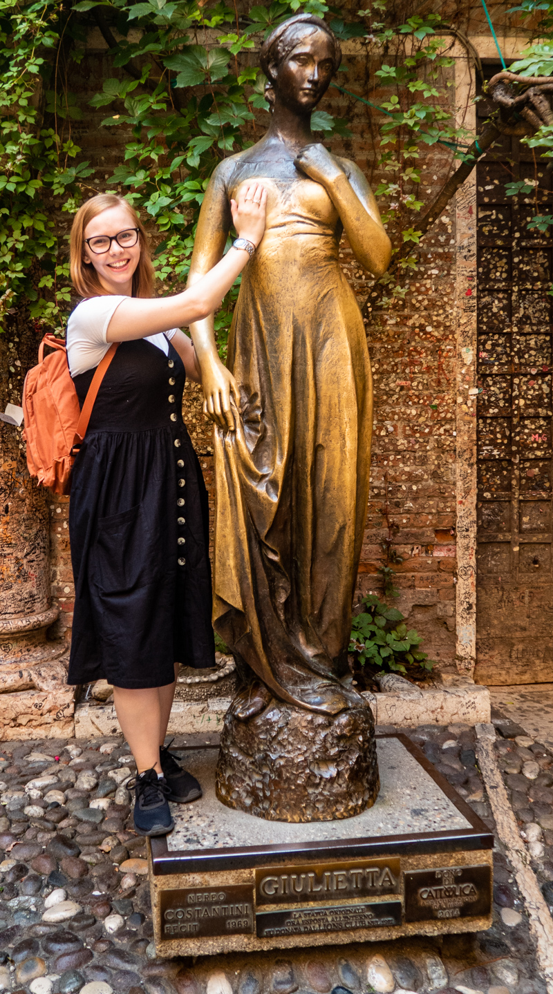 Almost Ginger blog owner posing with the Juliet statue in the courtyard of Casa di Giulietta in Verona, Italy