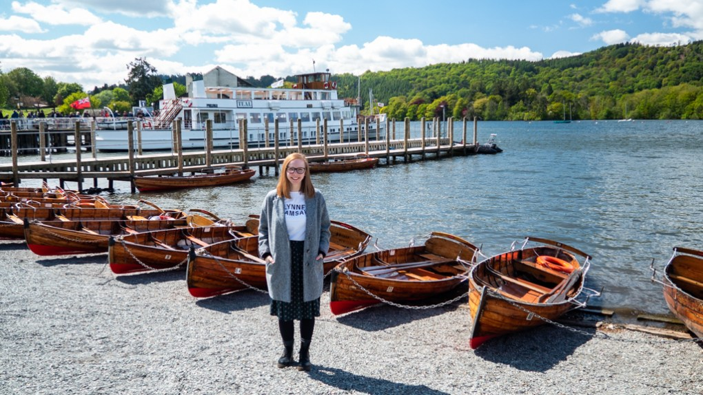 Almost Ginger blog owner next to boats on the banks of Lake Windermere in Bowness-On-Windermere in the Lake District, UK