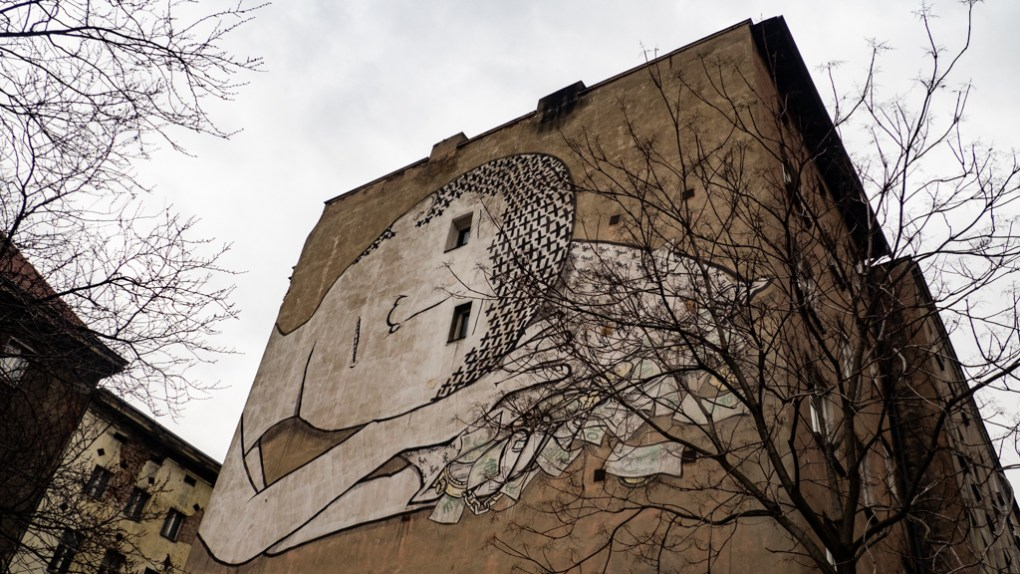 Large mural street art of a boy sleeping in Wrocław, Poland