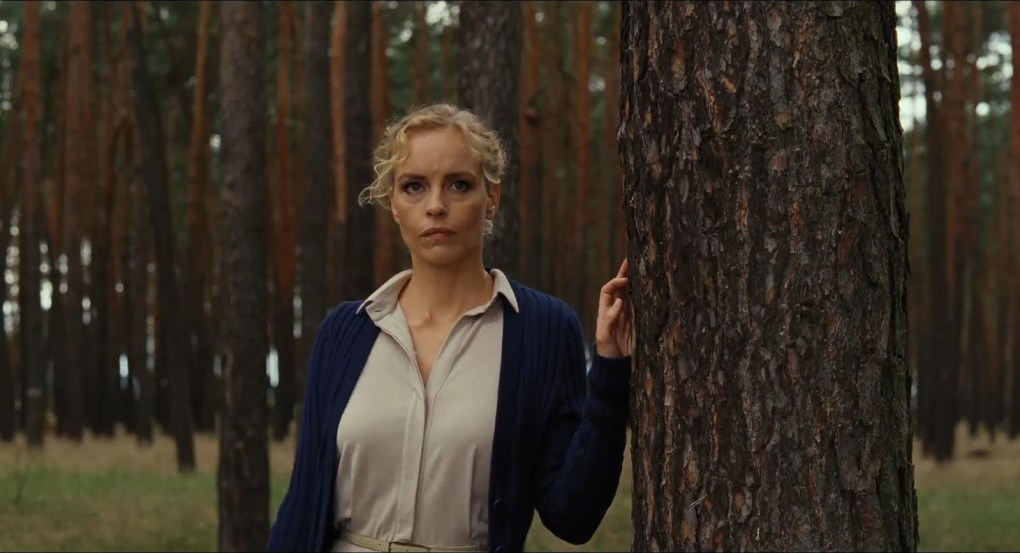 Film still from Barbara (2012) of a blonde woman leaning against a tree