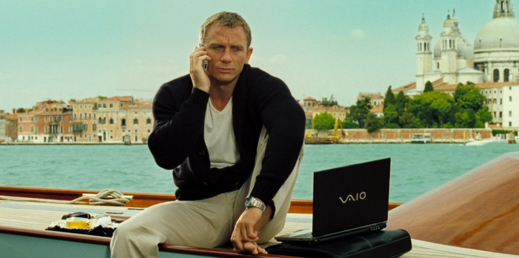 Casino Royale (2006) film still of James Bond using his phone and laptop on a boat in the Venice Grand Canal, Italy