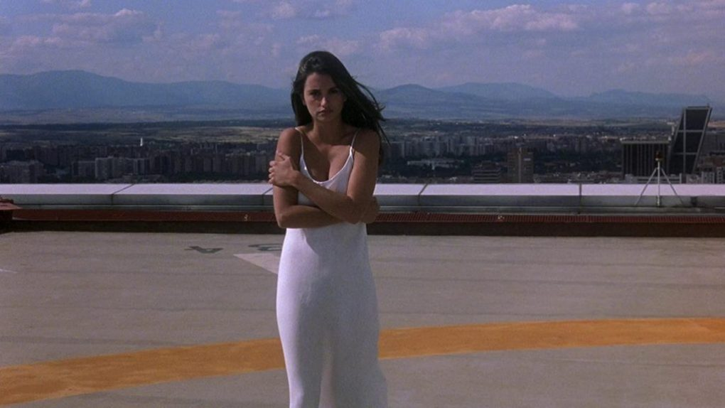 Open Your Eyes (1997) film still of Penélope Cruz hugging herself on a rooftop wearing a white slip dress in Madrid
