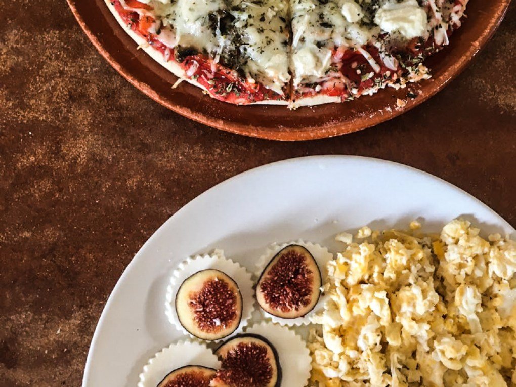 Figs, cheese, eggs and vegetarian pizza on a wooden table