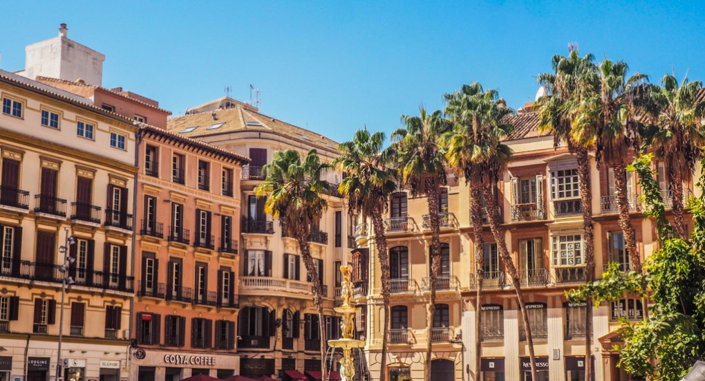 Plaza with Spanish style buildings and palm trees in Málaga, Spain