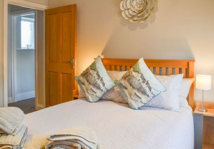Holiday house bed with cushions and towels