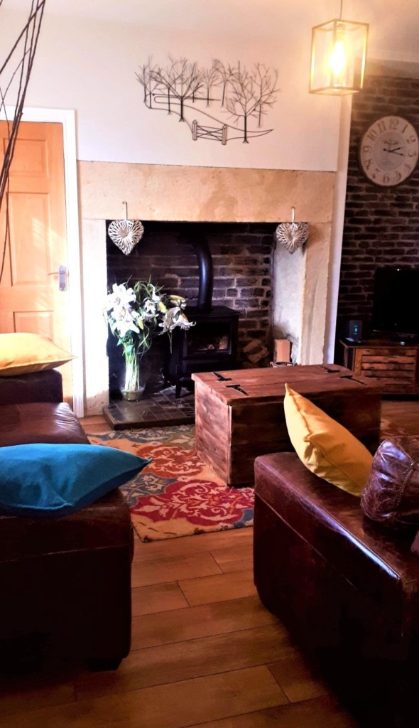 Living room with inglenook fireplace and electric real flame effect fire