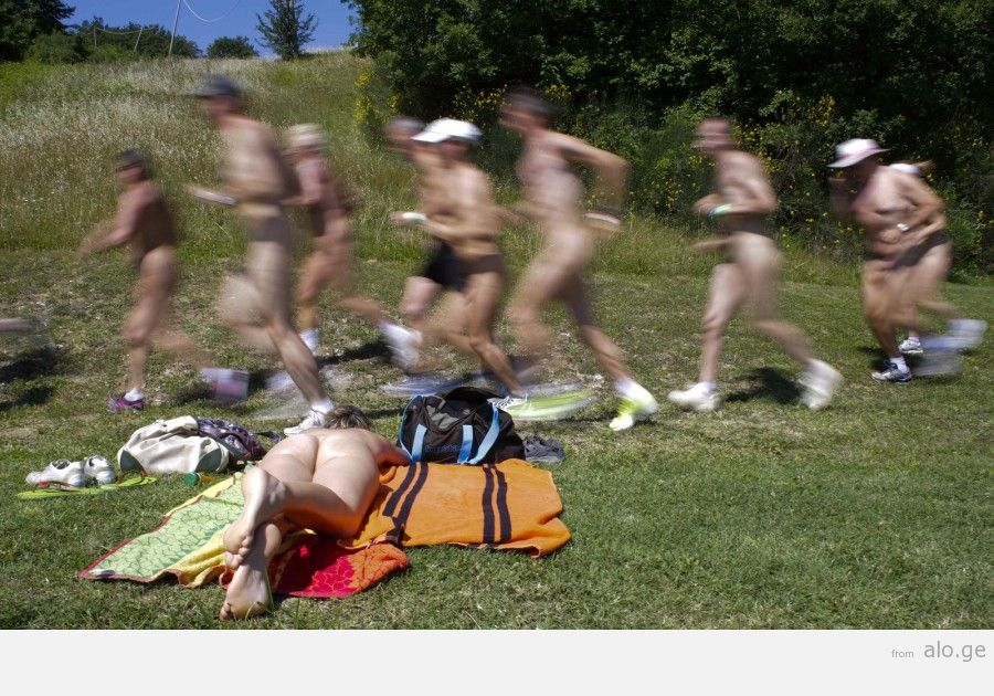 """People run during the """"www.inudisti.it"""" web community's annual gathering on private property at Oasis of Zello naturist resort near Bologna"""