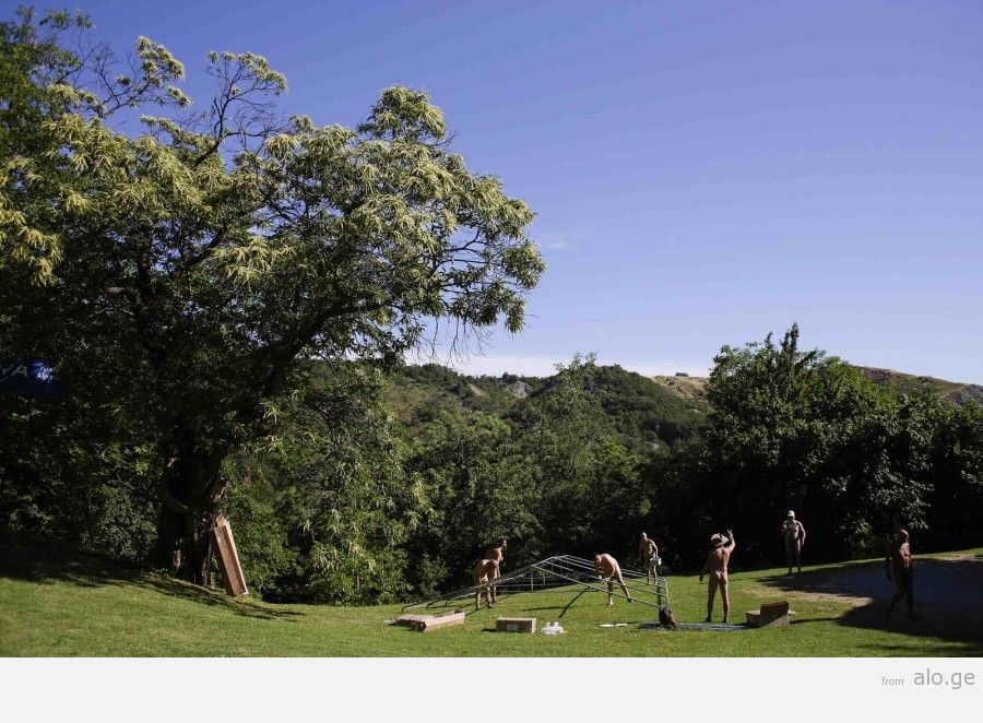 """A group of men start to set up a main tent during the """"www.inudisti.it"""" web community's annual gathering on private property at Oasis of Zello naturist resort near Bologna"""