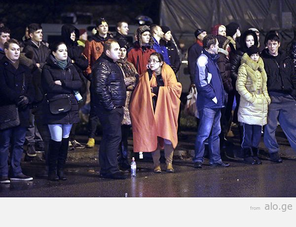 People gather near the collapsed Maxima supermarket in Riga