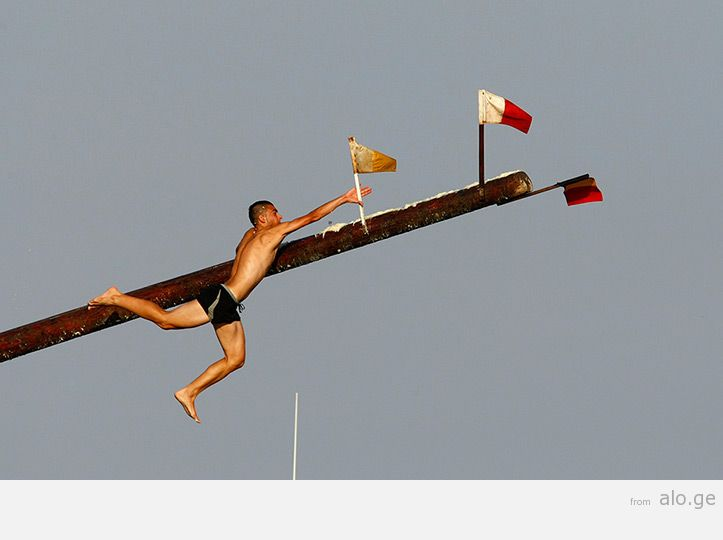 "A competitor grabs a flag as he slips off the ""gostra"" pole"