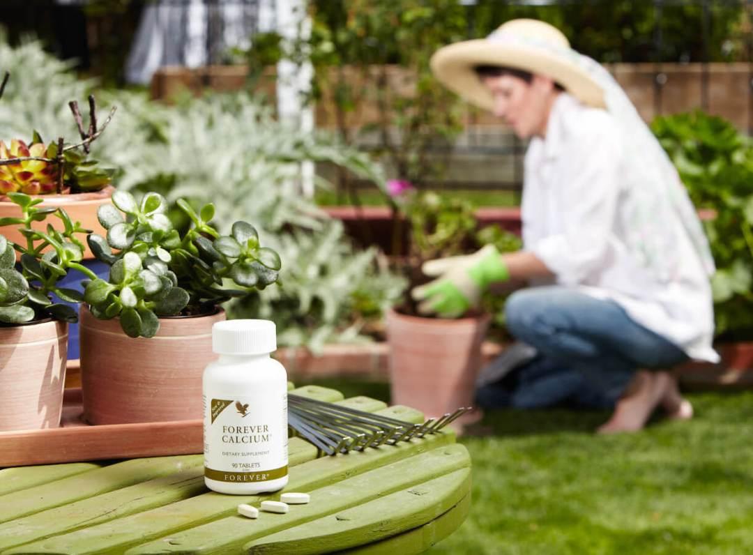 Forever Calcium na vrtnom stolu a u pozadini žena koja radi u vrtu