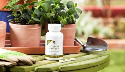 Forever Calciumn i tablete na vrtnom stolu sa cvijecem rukavicama i lopaticom