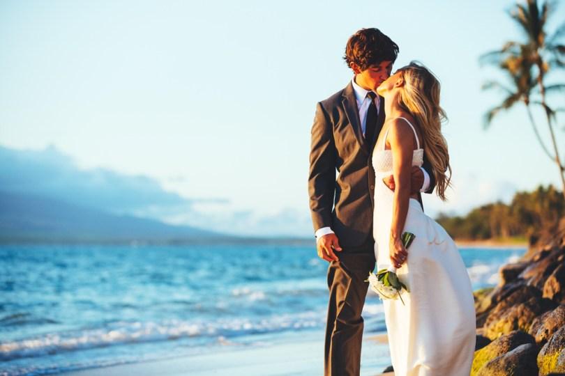 ハワイのビーチでキスをする新郎新婦