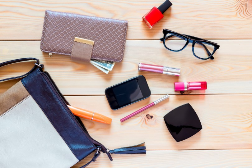 the contents of women's handbags are scattered on the floor