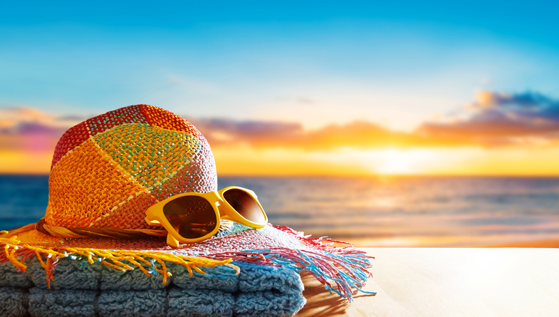 Summer vacation image with copyspace. Hat, yellow sunglasses on beach.