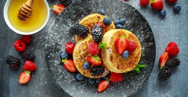 British Crumpets breakfast with blueberries, strawberries, blackberries, raspberries drizzled with icing sugar