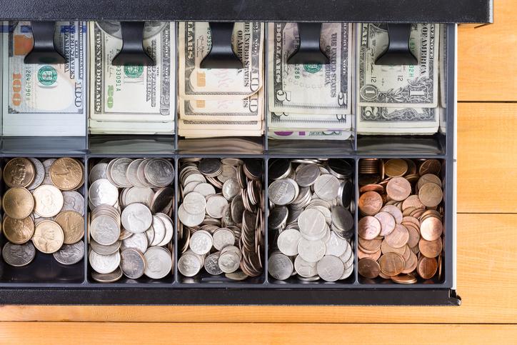 Open cash register drawer on wooden table