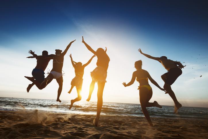 Happy friends sunset jump friendship holidays