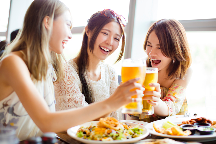 Group of girl friends toasting and eating in the restaura