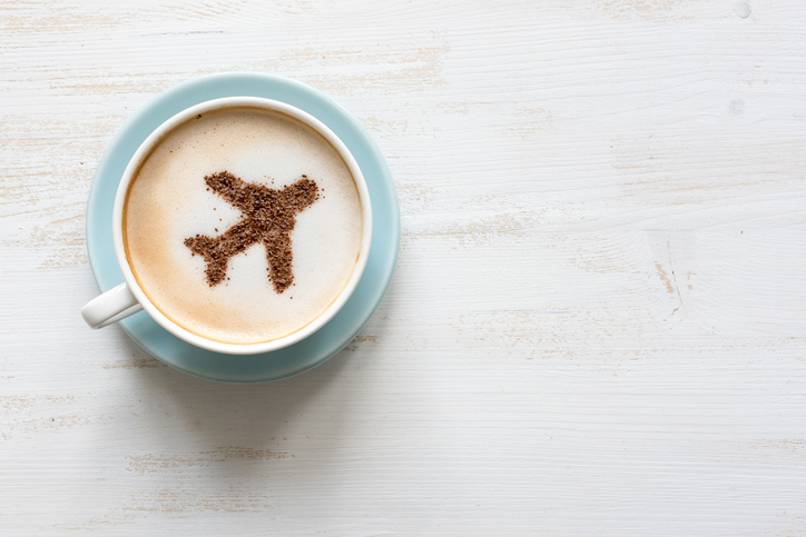 Airplane made of cinnamon in cappuccino , white background