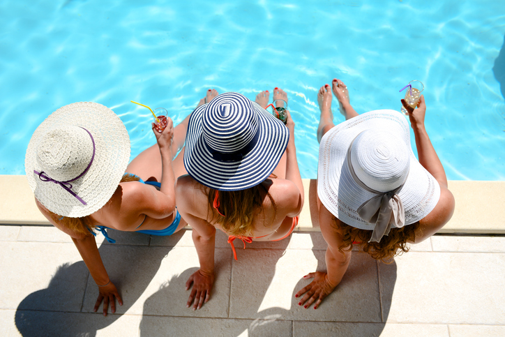 three beautiful young woman with sun hat sitting by the poolside of resort swimming pool during summer holiday