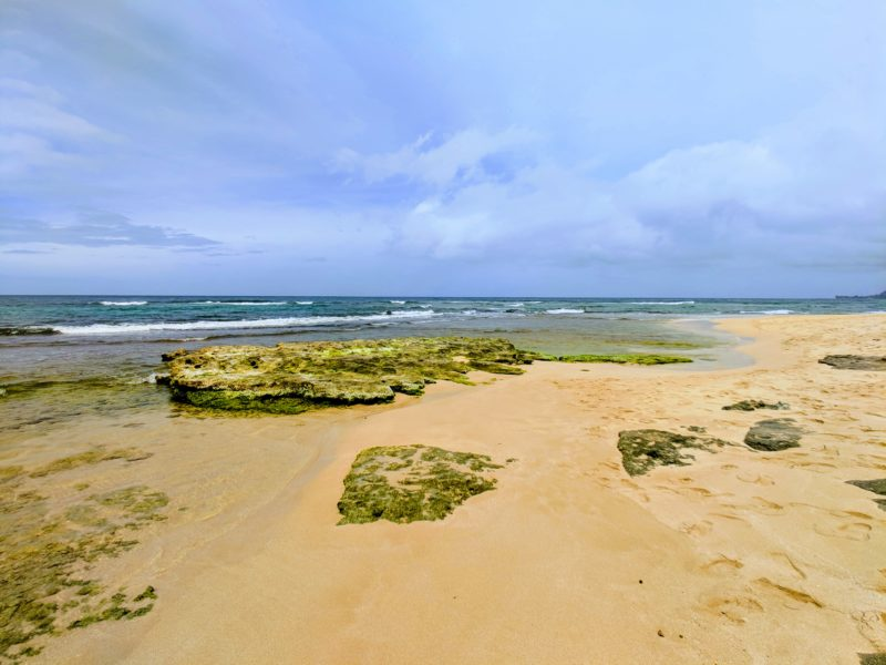 Where the rocks end and the sand begins at Papailoa beach. The Best Beaches In Oahu's North Shore For Families.