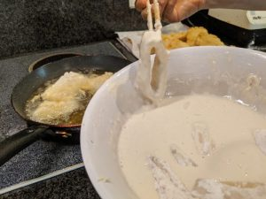 Cover the squid in the flour, then batter.