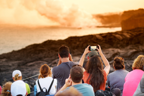 Hawaii Volcanoes National Park: Visitors watching lava pour into the ocean on the Big Island. Hawaii travel. Things to do on the Big Island. Things to do in Hawaii.