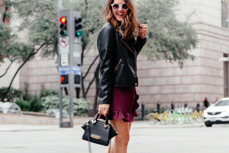 Spring Ruffle Hem: Dallas fashion blogger sharing a spring look featuring a ruffle hem wrap dress, white booties & sunglasses, & a leather moto jacket for an effortless transitional look.