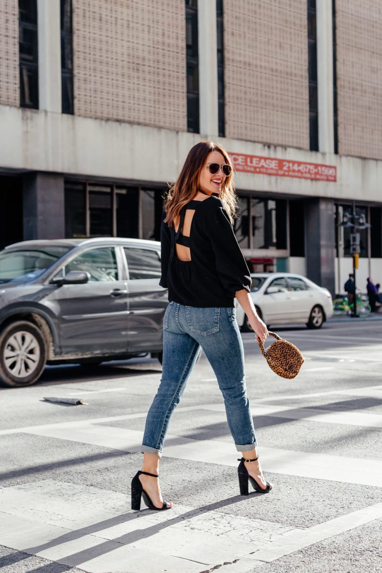 Open Back + Leopard: Dallas blogger sharing an open back black top paired with high waisted jeans, block heeled sandals, and a round leopard bag for a great spring date night look. #openback #leopard #datenightlook #springstyle
